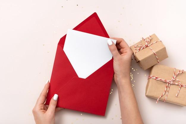 Vrouwelijke hand houdt lege vierkante papieren mockup-envelop rode kerst vast