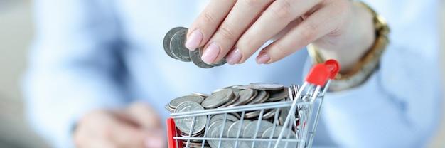 Vrouwelijke hand houdt munten vast over korst vol munten hoe we gedwongen worden om meer uit te geven
