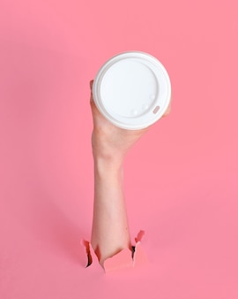 Vrouwelijke hand houdt papieren koffiekopje door gescheurd roze papier. minimalistisch concept