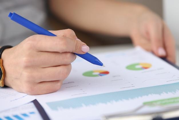 Vrouwelijke hand houdt pen over grafiek met bedrijfsrecords. zakelijke rapportage en ontwikkeling
