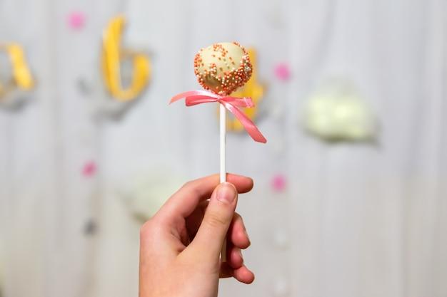 Vrouwelijke hand houdt pop cakes op pastel achtergrond. witte chocolade cake pop versierd met kleurrijke hagelslag. partij concept.