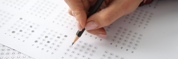 Vrouwelijke hand houdt potlood vast en markeert antwoorden om het concept van inhuren te testen