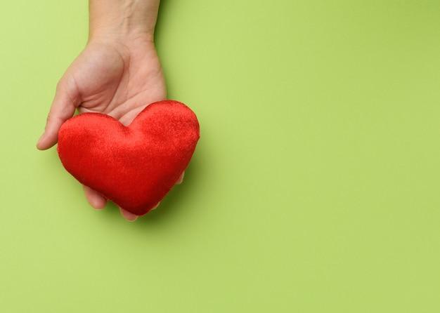 Vrouwelijke hand houdt rood textiel hart geïsoleerd