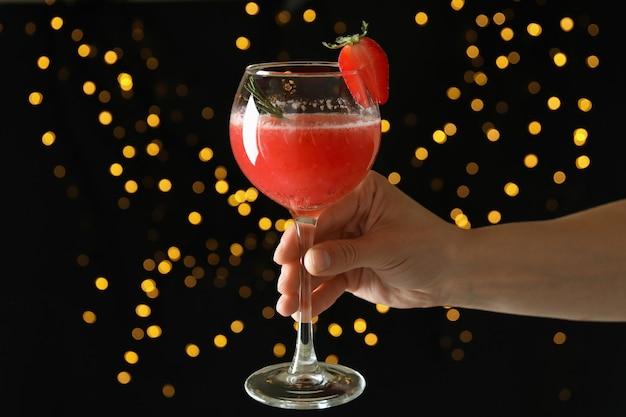 Vrouwelijke hand houdt rossini-cocktail vast op de achtergrond met wazige lichten