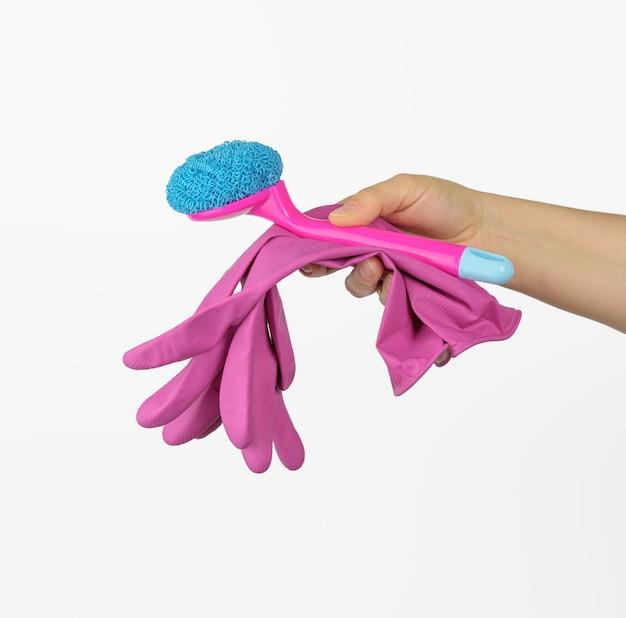 Vrouwelijke hand houdt roze schoonmaak handschoenen en een borstel op een witte achtergrond, close-up