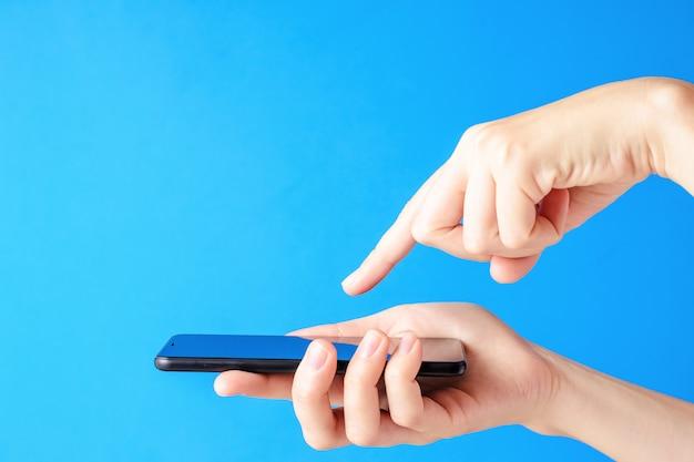 Vrouwelijke hand houdt smartphone op blauwe achtergrond. de mobiele vertoning van de vrouwenaanraking met vinger