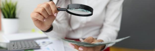 Vrouwelijke hand houdt vergrootglas en contant geld aan de werktafel vast