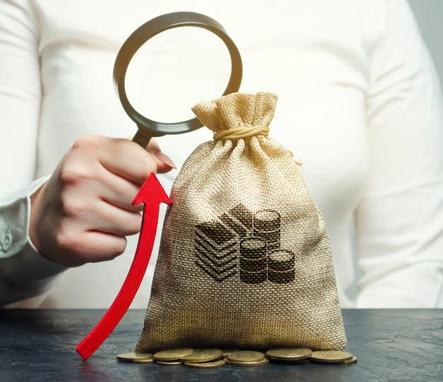 Vrouwelijke hand houdt vergrootglas over geld tas