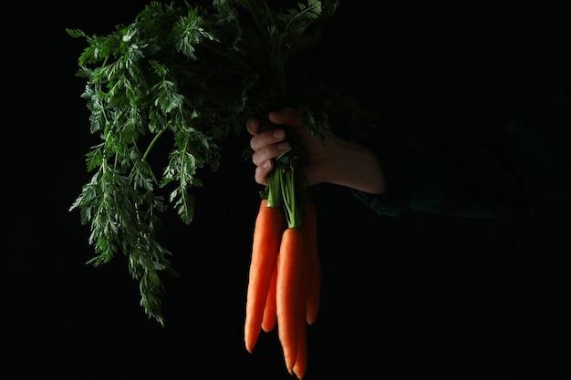 Vrouwelijke hand houdt verse wortel op donkere achtergrond