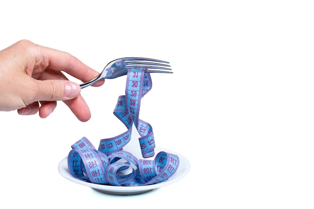 Vrouwelijke hand houdt vork met opgerolde meetlint over lege plaat geïsoleerd op wit