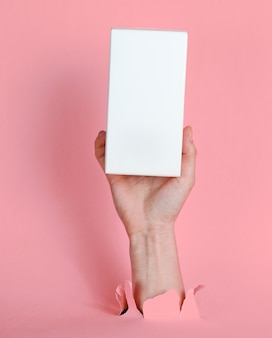 Vrouwelijke hand houdt witte doos door gescheurd roze papier. minimalistisch creatief mode-concept