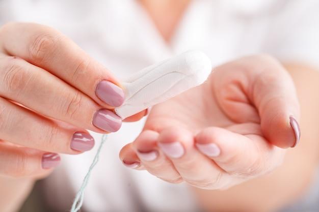 Vrouwelijke hand hygiënisch tamponpatroon