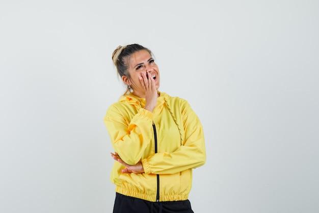 Vrouwelijke hand in de buurt van mond in sport pak en op zoek vrolijk, vooraanzicht.