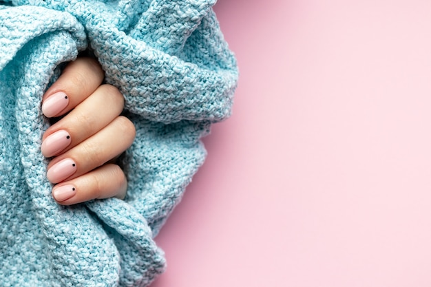 Vrouwelijke hand in een blauwe gebreide sweaterstof met trendy mooie manicure - roze nude nagels met zwarte kleine stippen op een roze achtergrond met kopie ruimte