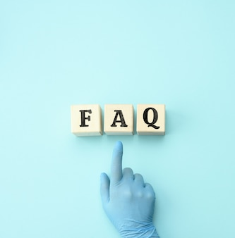 Vrouwelijke hand in een blauwe latex handschoen wijst naar houten blokken met het opschrift faq (veelgestelde vragen). uitleg, tips en instructies voor gebruikers, thema geneeskunde