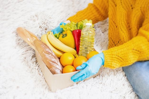Vrouwelijke hand in een blauwe medische handschoenen houden een kartonnen doos met veganistisch eten