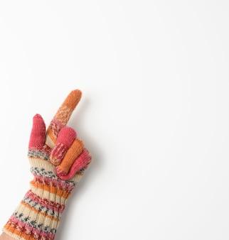 Vrouwelijke hand in een gebreide want op een witte achtergrond, wordt de wijsvinger opgewekt