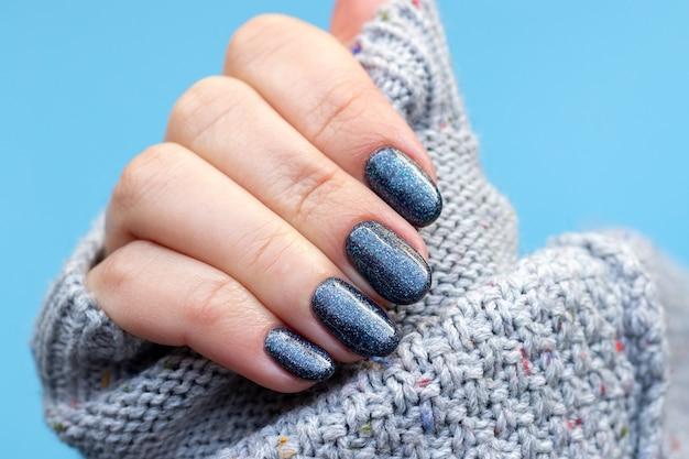 Vrouwelijke hand in een grijze gebreide sweaterstof met prachtige manicure - donkergrijsblauwe glinsterende nagels op blauwe achtergrond. selectieve aandacht. close-up uitzicht