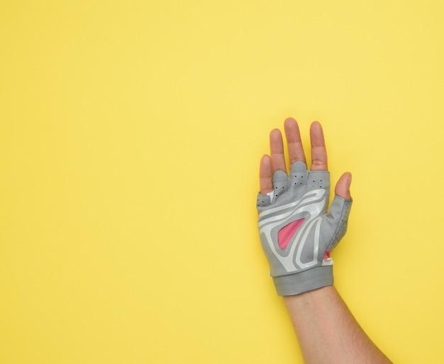 Vrouwelijke hand in een grijze handschoen voor eerbetoon aan sport en het besturen van een fiets op een gele achtergrond, palm is open