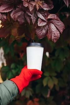 Vrouwelijke hand in een rode handschoen met een witte koffiekopje met stro op de achtergrond van druivenbladeren