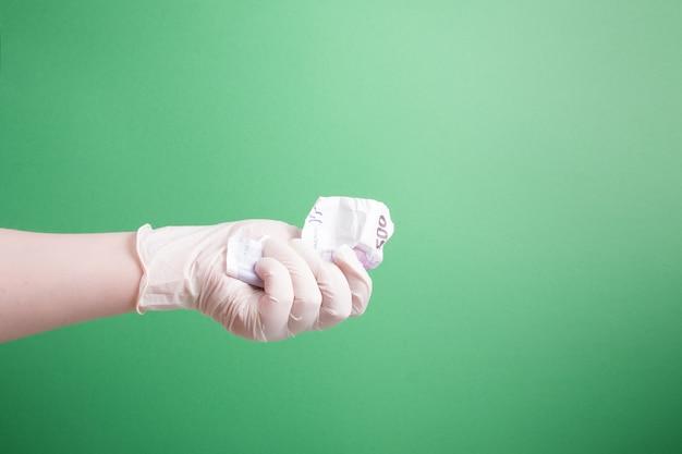 Vrouwelijke hand in een rubberen witte medische wegwerphandschoen houdt een verfrommeld biljet van 500 euro
