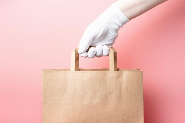 Vrouwelijke hand in een witte handschoen houdt bruine kartonnen zak, voedsel levering concept.