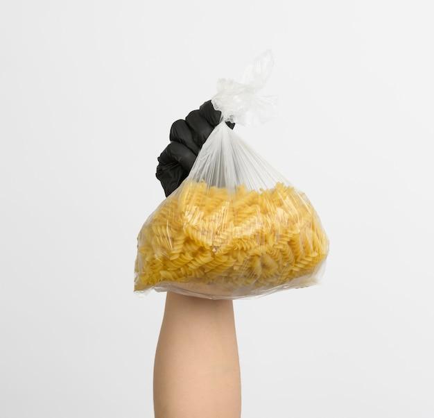 Vrouwelijke hand in een zwarte handschoen houdt een doorzichtige zak met rauwe fusilli pasta