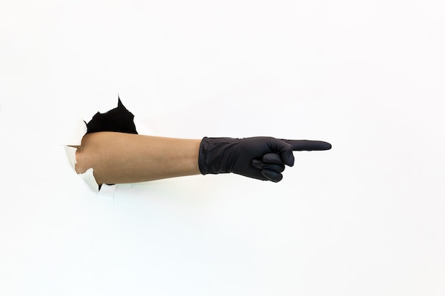 Vrouwelijke hand in een zwarte latexhandschoen door gescheurd papier op een witte achtergrond toont aanwijzingen