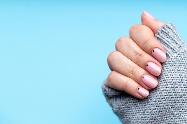 Vrouwelijke hand in gebreide trui met roze nude nagels met zwarte kleine stippen op blauwe achtergrond