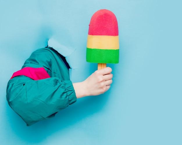 Vrouwelijke hand in het jasje van de jaren '90stijl houdend roomijs