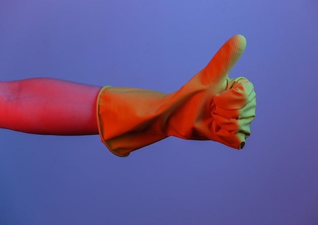 Vrouwelijke hand in latex handschoen toont duim. gradiënt neonlicht
