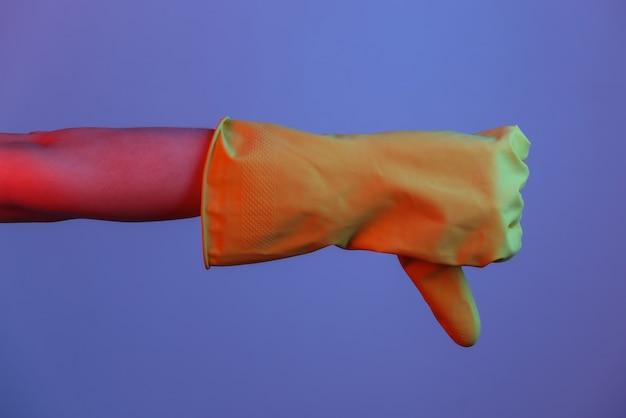 Vrouwelijke hand in latex handschoen toont duim naar beneden. gradiënt neonlicht