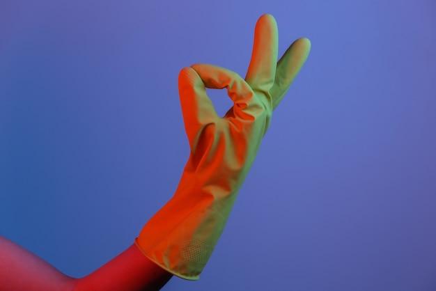 Vrouwelijke hand in latex handschoen toont oke symbool. gradiënt neonlicht