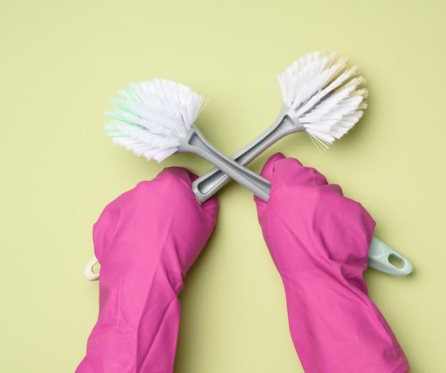 Vrouwelijke hand in paarse rubberen handschoenen houdt een plastic schoonmaakborstel op groene achtergrond, close-up