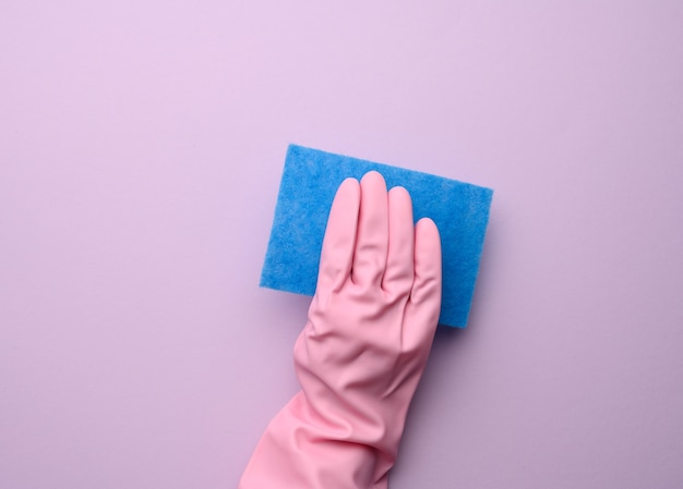 Vrouwelijke hand in roze rubberen handschoen houdt blauwe keukenspons op paarse achtergrond, close-up