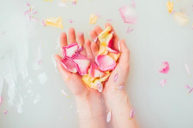 Vrouwelijke hand in water met bloemblaadjes