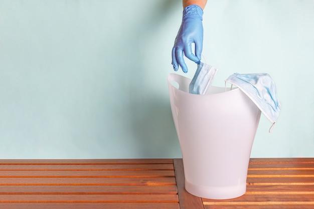 Vrouwelijke hand in wegwerp rubberen handschoenen gooit gezichtsmasker in vuilnisbak