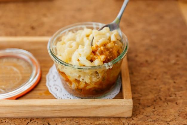 Vrouwelijke hand is het scheppen van macaroni cheese gebakken met vlees saus in glazen kom.