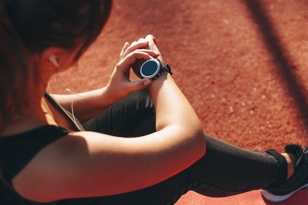 Vrouwelijke hand kijkt naar haar sporthorloge na het doen van cardio omdat ze 's ochtends buiten in een sportpark het dragen verliest terwijl ze op de grond rust.