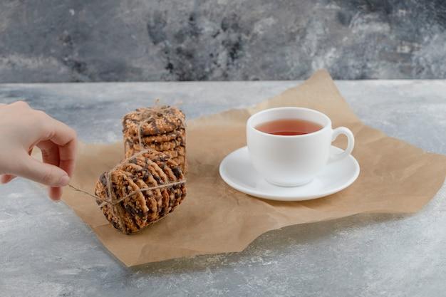Vrouwelijke hand koppelverkoop stapel koekjes op marmeren achtergrond.