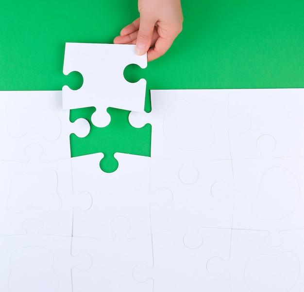 Vrouwelijke hand legt lege witte grote puzzels op een groen oppervlak