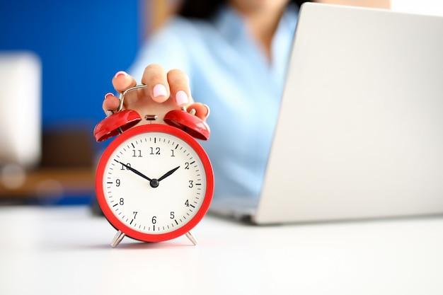 Vrouwelijke hand ligt op rode wekker naast laptop. werk op afstand freelance en deadlines concept