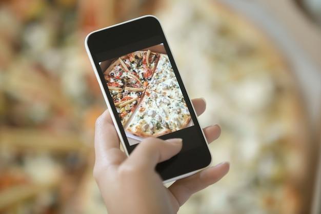 Vrouwelijke hand maken een foto van pizza
