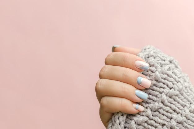 Vrouwelijke hand manicure close-up met gebreide trui. trendy geometrische nagelkunstmanicure. manicure salon banner concept