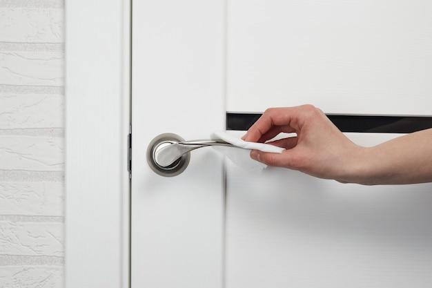 Vrouwelijke hand met antibacteriële vochtige doek voor het desinfecteren van deurklinken.