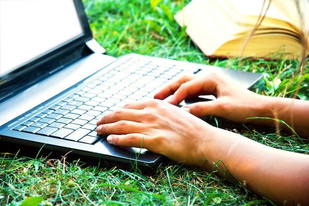 Vrouwelijke hand met behulp van een laptop buitenshuis.