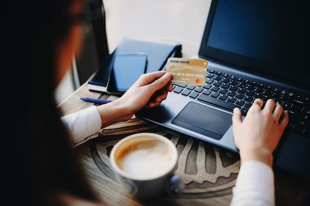 Vrouwelijke hand met behulp van een plastic creditcard en een laptop voor online transactie tijdens het drinken van een kopje koffie in een coffeeshop.