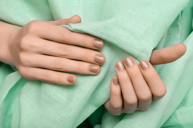 Vrouwelijke hand met beige glitter nagel ontwerp
