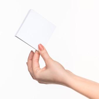 Vrouwelijke hand met blanco papier voor records op wit met juiste schaduw