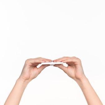 Vrouwelijke hand met blanco papier voor records op wit